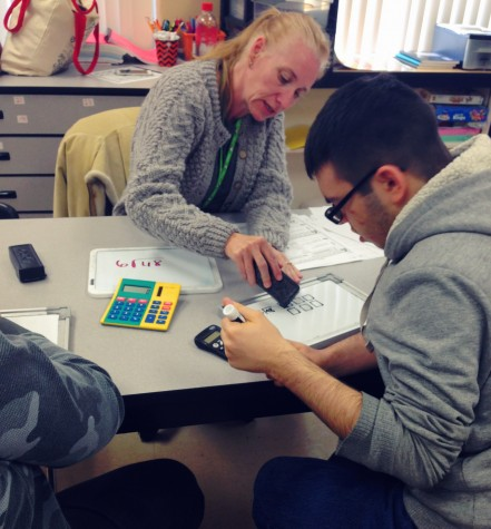 Instructor Joscelyn Wildgen teaches ESE student John Rivera about square roots in an interactive math lesson.