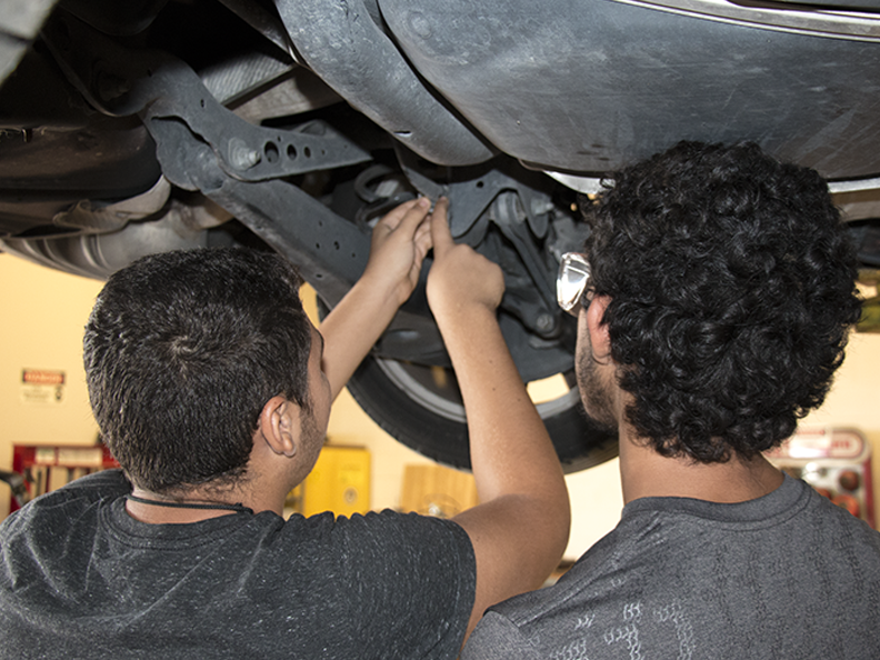 Automotive students work on a car on a lift during class.