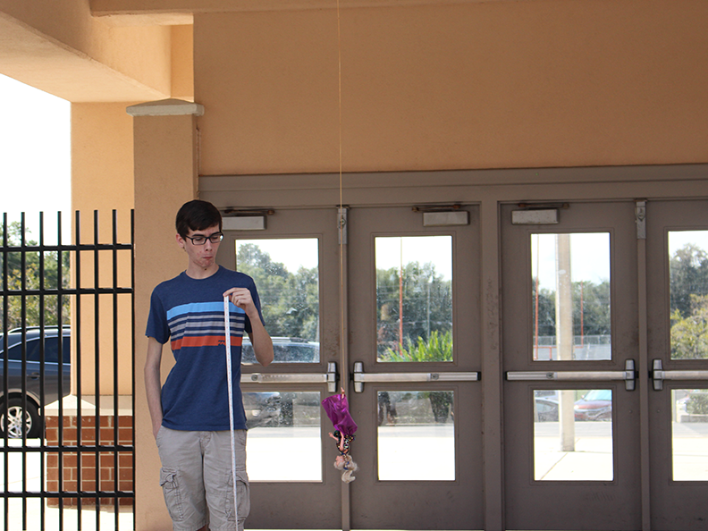 Junior Scott Wolfe measures the drop of the barbie doll as it was thrown down from above.