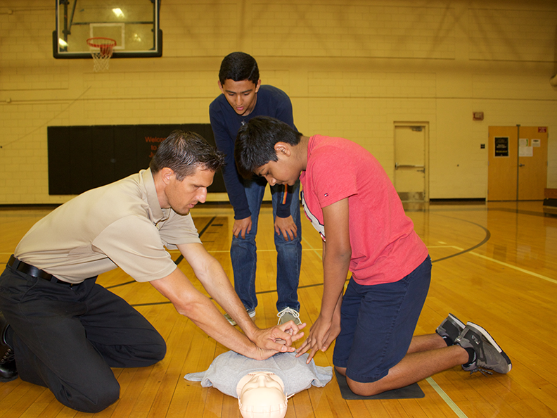Division Chief of Training and EMS Nick Dorey shows freshmen Jose Bolanos and Sahas Thyarala how to perform CPR compressions.