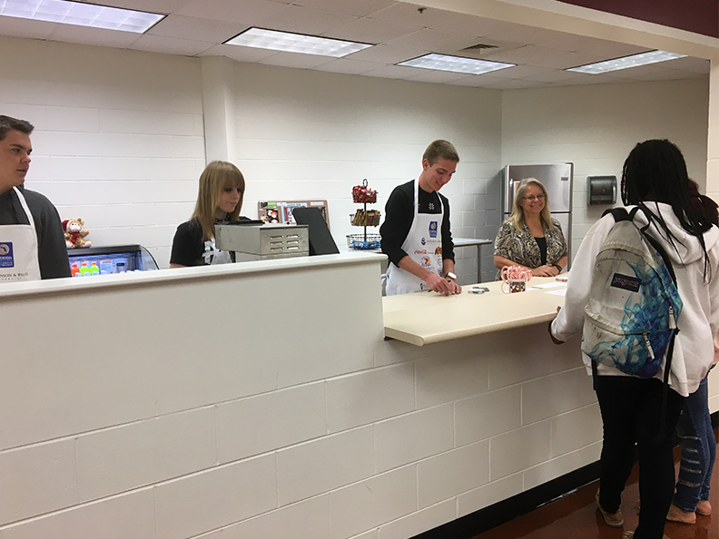 Students work alongside culinary teacher Karen Stapleton during the soft opening of the Lion's Den Cafe.