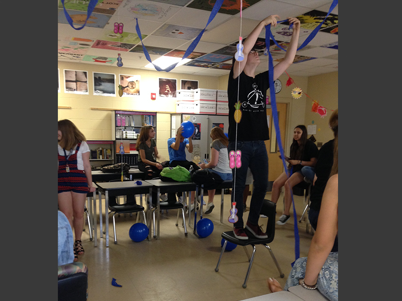 Junior Seth Pisano hangs decorations in adviser Shayna Hron's room for preparation of the Jewish Student Union's end of the year party on May 19, 2017.
