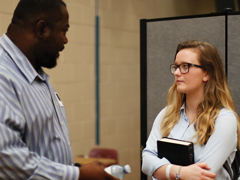 Senior Anna Wampler talks to optical engineer Rodney Jackson after the official presentations at the Career Day event on Feb. 8 at the RWL gym.