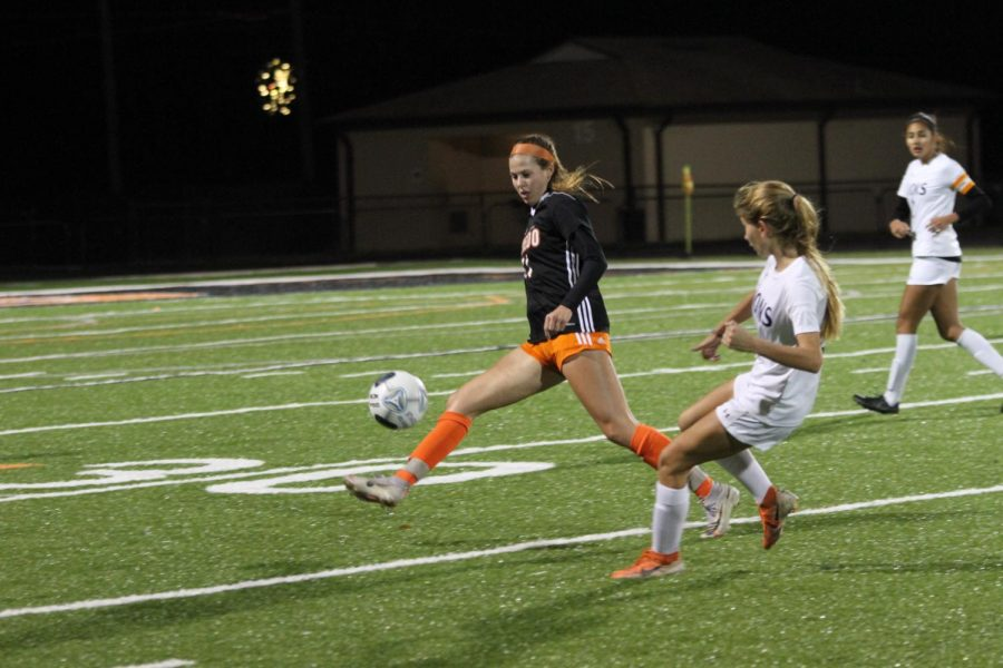 KICKING QUEEN: Junior Kyleigh Thelen clears the ball against an opposing player in a home game. Thelen is a center back on the girls varsity team.